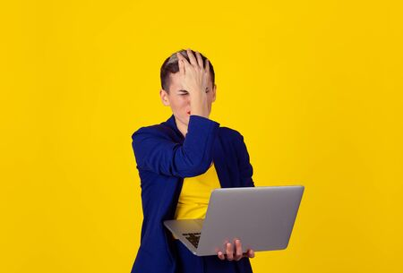 Stressed caucasian overwhelmed woman with computer in hand. Multicultural Latina girl short hair red lips blue suit yellow shirt isolated yellow background with copy space. Negative emotion reaction