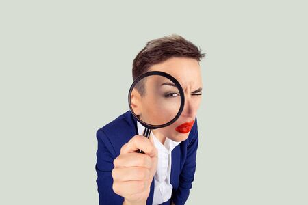 Investigator. Meticulous detective curious business analyst concept. Closeup macro face expressive curious girl looking through magnifying glass isolated light green white background
