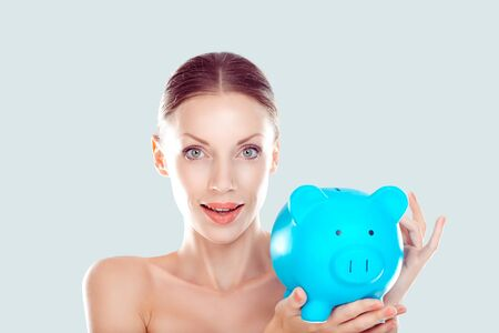 Closeup portrait happy, smiling excited natural makeup woman holding piggy bank isolated on light blue white wall background. Financial savings, banking concept. Positive emotions, face expressions