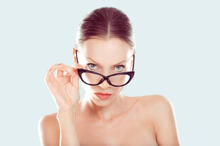 Skeptical. Closeup portrait beautiful young woman, lady looking at you camera over glasses gesture skeptically, isolated light blue background. Negative human emotions, facial expression body language