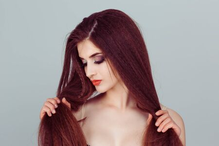I love my hair. My hair is my wealth an beauty. A woman looks at her hair,  shows her hair color or looks something. On grey background