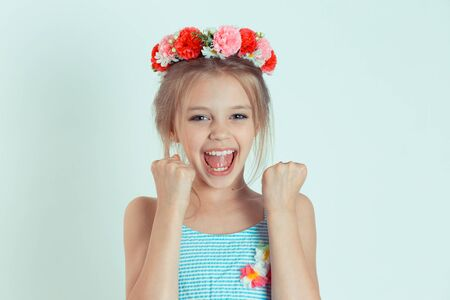 Happy kid girl hands cheering, celebrating, pumping fists looking at camera happily. Closeup portrait of Caucasian kid model with floral headband isolated on white green gray copy space background. Reklamní fotografie