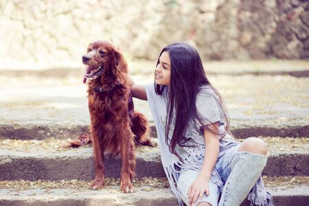 Pretty young brunette embracing looking at adorable dog while sitting on stone steps in park and smiling happily at camera.