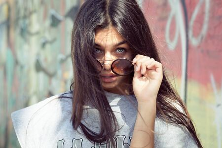Surprised frustrated young woman holding sunglasses down skeptically graffiti wall on background Imagens