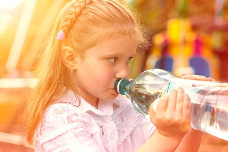 I am Thirsty. Closeup portrait little cute girl drinking mineral water from her bottle isolated outside, outdoors park background. Retro toned, orange golden sunset Banco de Imagens