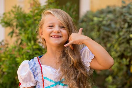 Cute little blonde girl child shows by gesture that she speaks on the phone smiling toothless isolated green shrubs nature garden near house outdoors on the background