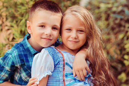 Schwester mit Bruder zeigt Zuneigung, umarmt und lächelt isolierte Natur grüner Strauchbaumhintergrund