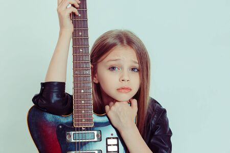 I want to be a rocker but I cannot play, sing. Closeup portrait Sad upset woman holding electronic guitar looking at you camera isolated light green white background wall, studio shot horizontal image Imagens