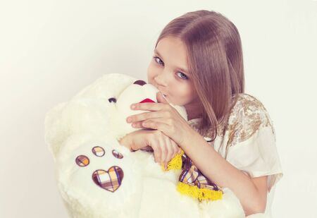 I love my teddy bear. Close up portrait cute girl holding embracing kissing teddy bear eyes closed isolated white background looking at you camera. Love care family concept