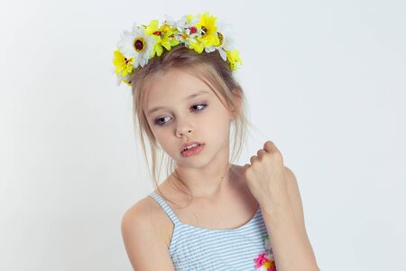 Little fashionista. Closeup beautiful little girl kid, wreath of yellow flowers floral head band on head light blue dress shirt posing in studio hand up thinking isolated white grey background Stockfoto