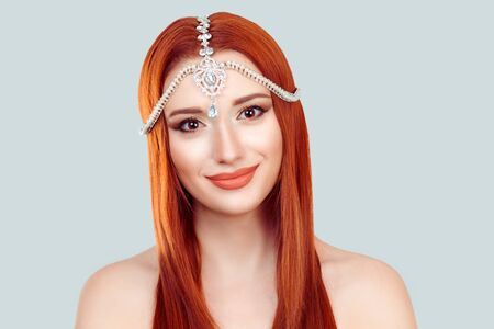 Beautiful and happy. Portrait of cute indian style red head girl with tikka on head. Positive human emotions and facial expressions.
