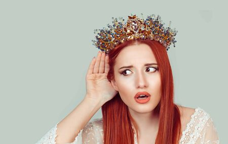 Eavesdropping bad news. Sad frustrated unhappy woman listening ear to bad news or having hearing impair hard of hearing pretty girl with crystal crown on head isolated on light green background wall Banque d'images