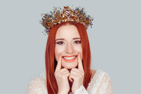 Beauty smiling fresh woman face with the health teeth. Pretty girl beauty queen showing perfect smile with hand fingers pointing touching crystal crown on head isolated on light gray background wall 版權商用圖片