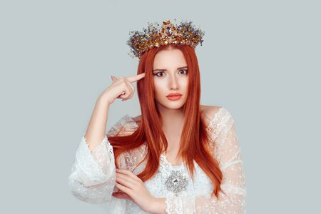 Angry mad beauty queen gesturing with finger against temple telling you are crazy? think about it pretty woman pointing at her head with crystal crown on head isolated on light gray background wall