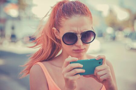 Portrait of an annoyed and frustrated young woman looking at phone isolated on city scape background. Human emotion face expression feeling