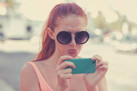 Upsetting message. Portrait of an annoyed and frustrated young woman looking at the phone isolated on city scape background. Negative human emotion face expression feeling