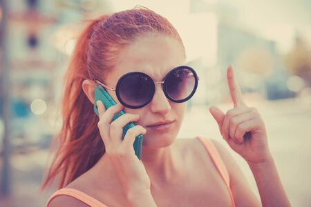 Attention, listen to me. Close up portrait of young unhappy frustrated woman wagging finger talking at phone on city scape background. Negative human emotions face expression feelings body language.