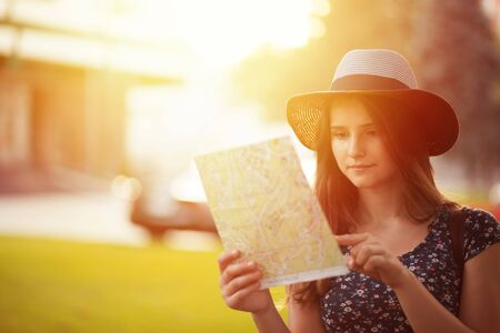 Tourist. Serious Woman in hat looking at the map searching for landmark isolated city center on background at sunset in summer. Tourism concept Stockfoto