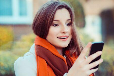 wow, dobra wiadomość na ekranie. Zbliżenie zaskoczony krzyczy młoda dziewczyna patrząc na telefon, widząc nowe zdjęcia z zabawnymi emocjami na twarzy na białym tle poza miastem. Ludzka emocja, reakcja, ekspresja