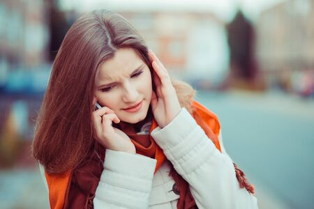 I do not hear you. Closeup portrait beautiful woman girl talking to the phone listening carefully trying to hear understand the conversation isolated city scape blurred background of Brussels Belgium