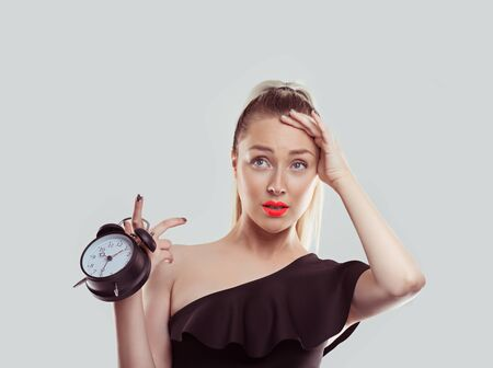 Oh, I forgot to change the time I got a date and it is already late. Young woman holding alarm clock stressed running late isolated white light grey background wall