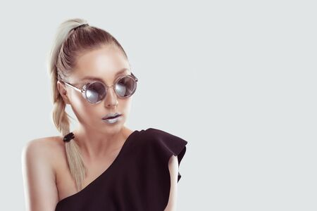 Young beautiful stylish woman model, blonde ombre hair plait wearing black open shoulder dress Grey metallic lipstick trendy round mirrored sunglasses looking aside. Copy-space. Beauty fashion concept