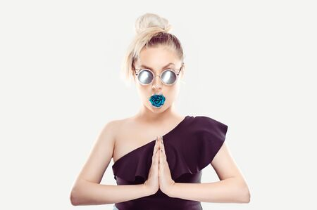 I am so cool and fashionable. The woman holds her hands on her chest in yoga pose, wears gray mirror sun glasses, has a blue green rose in her mouth blonde dark ombre gradient hair on White background Banco de Imagens