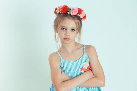 Cranky girl looking at camera with arms crossed, folded hands. Closeup portrait of Caucasian kid model with floral headband isolated on white green gray copy space background. Horizontal image.