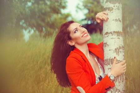 Smiling woman looking up near trees at park during a summer walk. Banque d'images