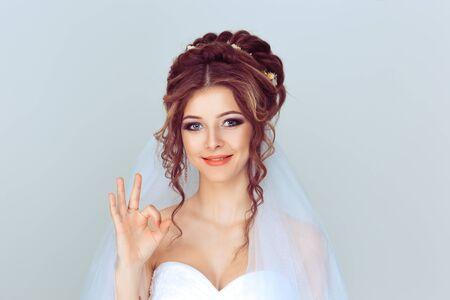 Schöne glückliche junge Frau des Porträts, die Okay-Zeichen mit der Hand zeigt, die auf hellblauem Wandhintergrund lokalisiert wird. Positive menschliche Emotionen Gesichtsausdruck Körpersprache