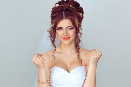 Angry bride. Closeup portrait upset young woman showing fists about to punch hit someone or to have nervous atomic breakdown isolated light blue background. Negative emotions face expression feelings