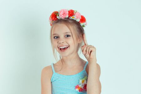 Closeup portrait intelligent excited young woman who just came up with idea aha. Caucasian kid model with floral headband isolated on white blue gray copy space background. Stock Photo