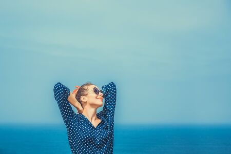 Woman enjoying the sea. Closeup portrait beautiful happy free young woman fashion enjoying nature peace arms outspread in sky isolated seascape ocean