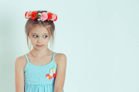 Portrait of confused funky kid made mistake have her lips pouted plump say oops feel frustrated looking to side anxious. Caucasian kid model with floral headband isolated on light green background