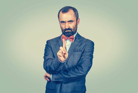 unhappy, serious man gesturing a no sign. Guy raising finger up saying oh no you did not do that. Negative emotion face expression. Portrait Mixed race bearded model isolated on light green background