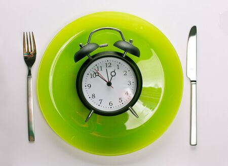 Time for lunch break concept. Alarm clock on a light green plate with fork and knife Cutlery isolated on white gray. Kitchen concept restaurant menu meal artistic background Фото со стока