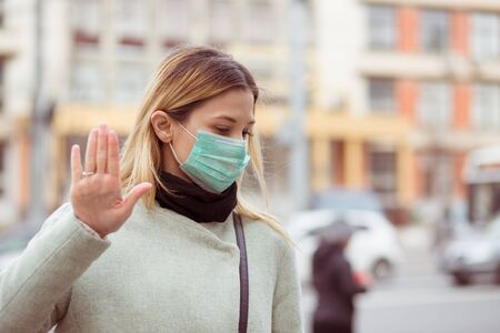 Young female doctor woman wearing sterile protective medical mask, making stop it there sign gesture with hand say signaling No standing on urban city background refusing to catch virus disease by air