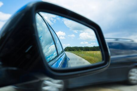 Side rear-view mirror car reflection of a winding road in a forest or countryside. Dramatic scenery Imagens