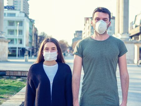 Girl and guy with masks to protect her from Corona virus. Woman and man with medical mask standing in front of clinic building in the city street. Different masks kind. Coronavirus pandemic concept Stock fotó