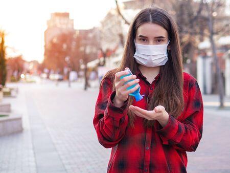 Serious Woman using, applying sanitizer from portable bottle for disinfect hands, girl in protective face mask. Disinfection, disinfecting hands against coronavirus, virus, bacteria. Pandemic covid-19