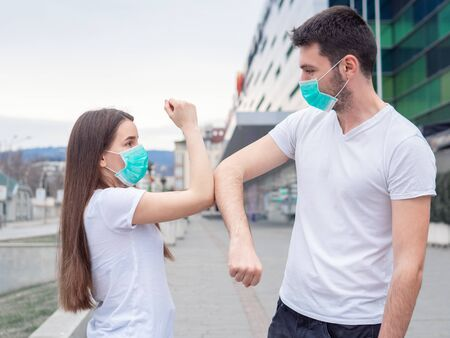 Two people woman and man wearing medical mask, friends greet each other with their elbows, instead of shaking hands. Elbow bump. A new greeting way to avoid the spread of coronavirus.