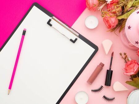 Clipboard and makeup tools and cosmetic products and roses flowers around it isolated on a pink and peach color background. Flat lay, top view copy space. Feminine beauty blogger workplace concept.