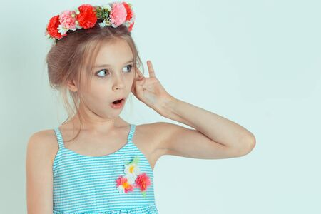 Shocked kid girl hand to ear eavesdropping listening to shocking news. Closeup portrait of Caucasian kid model with floral headband isolated on white blue gray copy space background. Horizontal image Foto de archivo