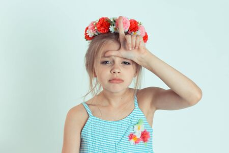 Closeup portrait young unhappy kid girl giving loser sign on forehead looking at you disgust on face isolated on white light green wall background. Negative human emotion face expression body language