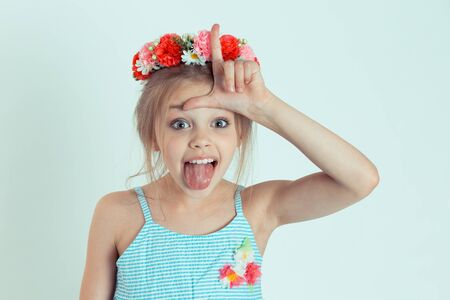Closeup portrait young unhappy girl, kid giving loser sign on forehead looking at tongue out isolated on light green wall background. Negative human emotion facial expression body language reaction