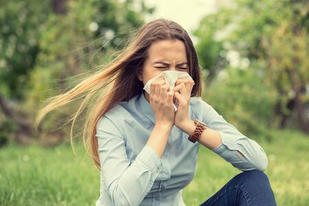 Brunette girl woman sneezing in a tissue blowing her runny nose outdoors, outside background Standard-Bild