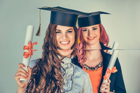 Portrait closeup beautiful happy graduates, two graduated student girls, young women in cap gown turning smiling holding diploma scroll isolated green background wall. Celebrating graduation ceremony