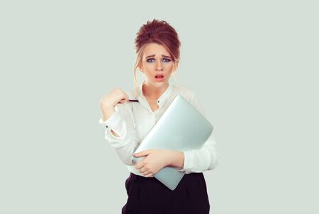 you mean me? Portrait angry unhappy annoyed young business woman holding laptop pointing with pen getting mad asking question you talking to me? Isolated light green background. Negative emotions