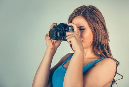 Photographer. Closeup portrait head shot young woman lady girl taking pictures with retro, vintage style dslr camera isolated green background wall. Wedding travel photography hobby, paparazzi concept