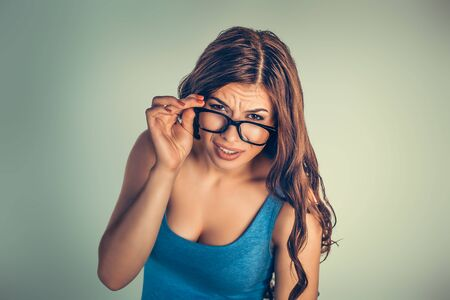 Closeup portrait beautiful young woman, lady looking at you camera over glasses gesture skeptically, isolated very green background. Negative human emotions, facial expression, feeling, body language
